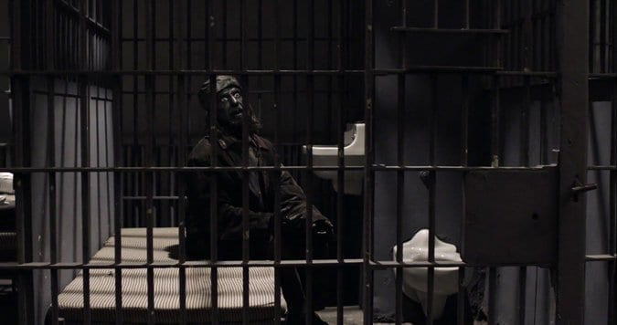 A completely blackened Woodsman in a prison cell