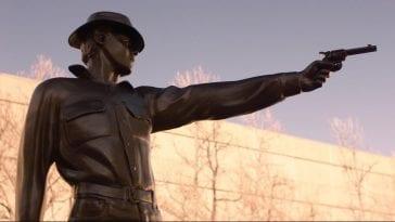 Bronze statue of a cowboy shooting his gun