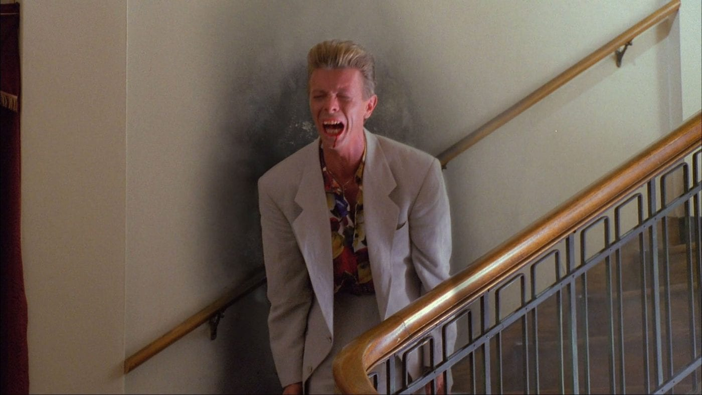 Phillip Jeffries (David Bowie) cries out with anguish as he appears on the stairs of a hotel