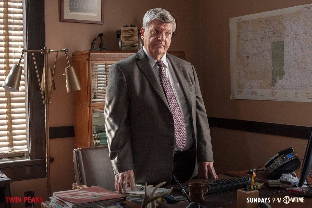 detective mackley stands at his desk