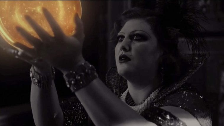 Senorita dido gazes at a ball of golden light and holds it in the air