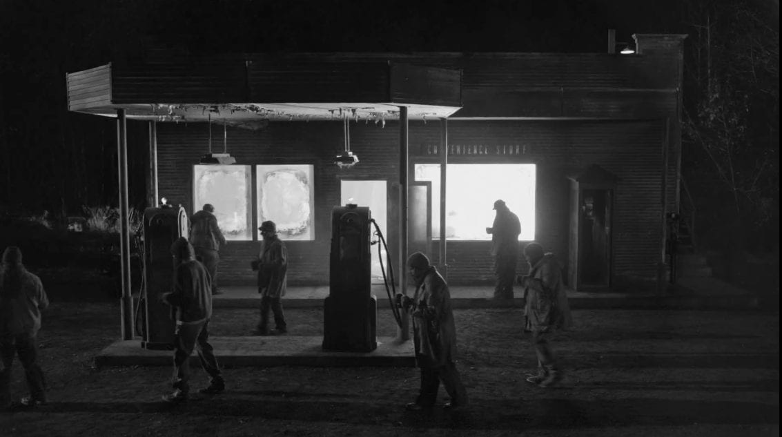 The woodsmen a borne outside a convenience store which is lit from within