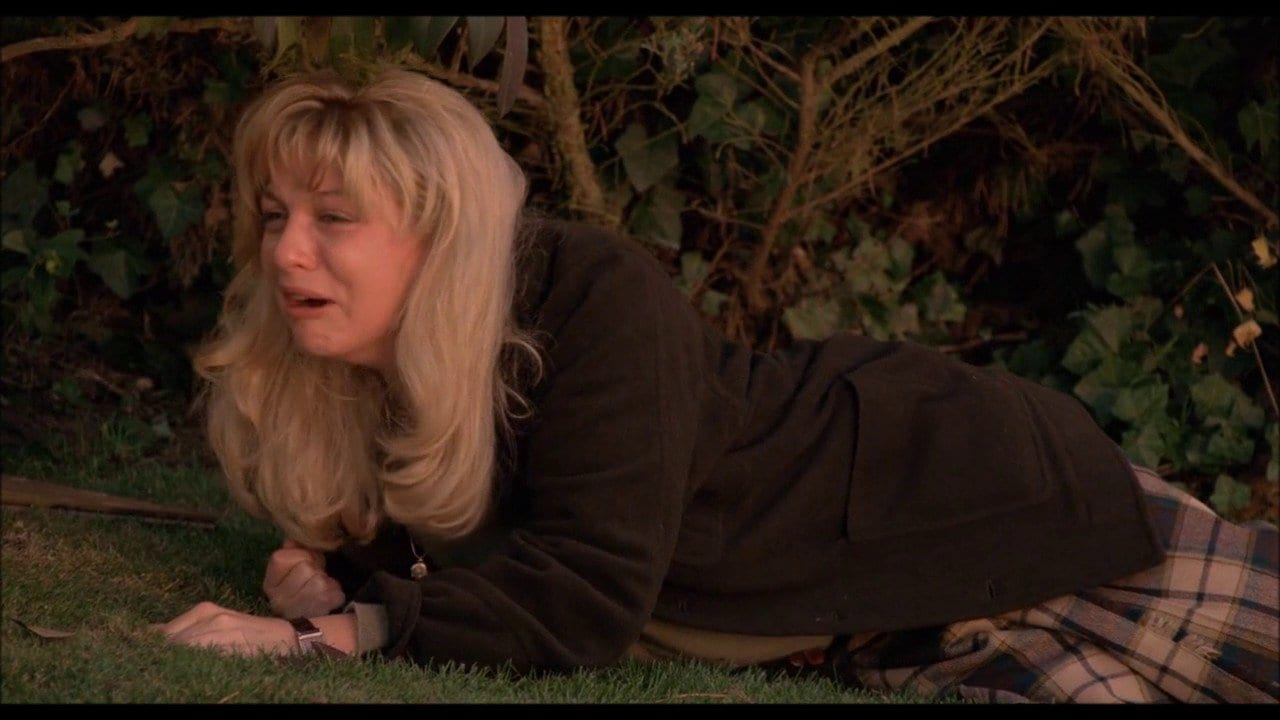 Laura Palmer lying on grass outside her home crying