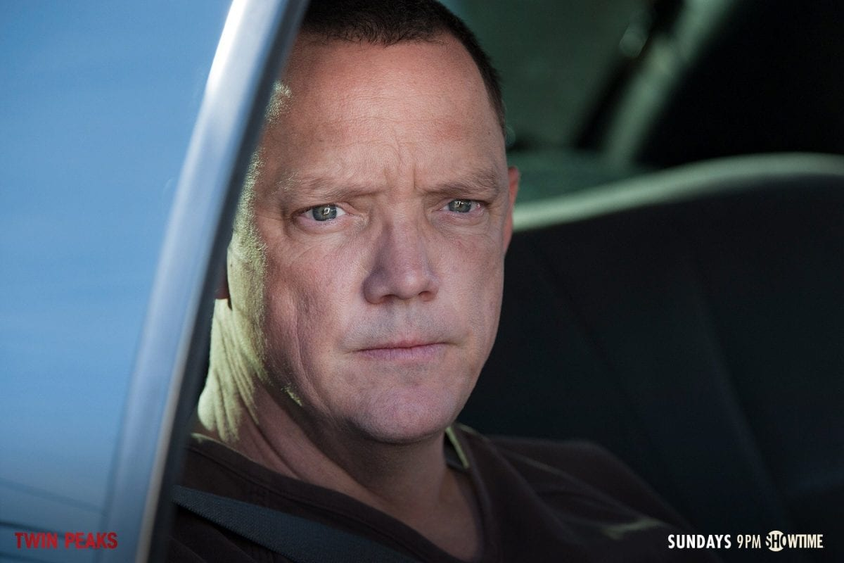 Bill Hastings sits in the back of a police car looking worried