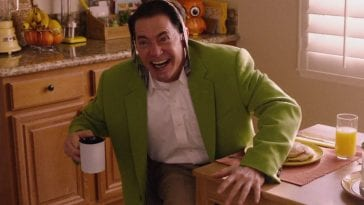 "Dougie Jones after spitting out coffee and saying ""Hi!"" He wears a green coat, his tie is tied around his head, and he leans forward holding his coffee cup."