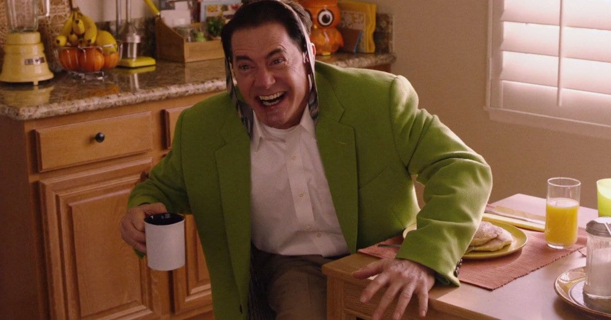 """Dougie Jones after spitting out coffee and saying """"Hi!"""" He wears a green coat, his tie is tied around his head, and he leans forward holding his coffee cup."""