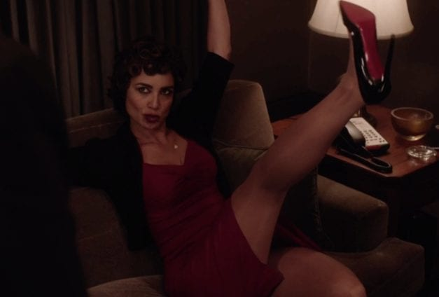 a very attractive french woman in a burgundy dress raises her leg in the air while wearing a stiletto
