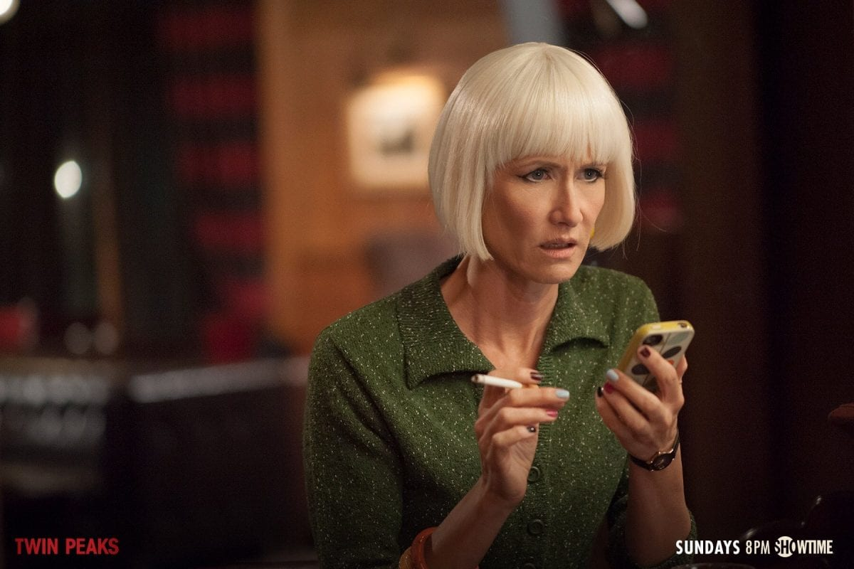 Diane smokes a cigarette and looks shocked at what she's read on a text message on her cell phone
