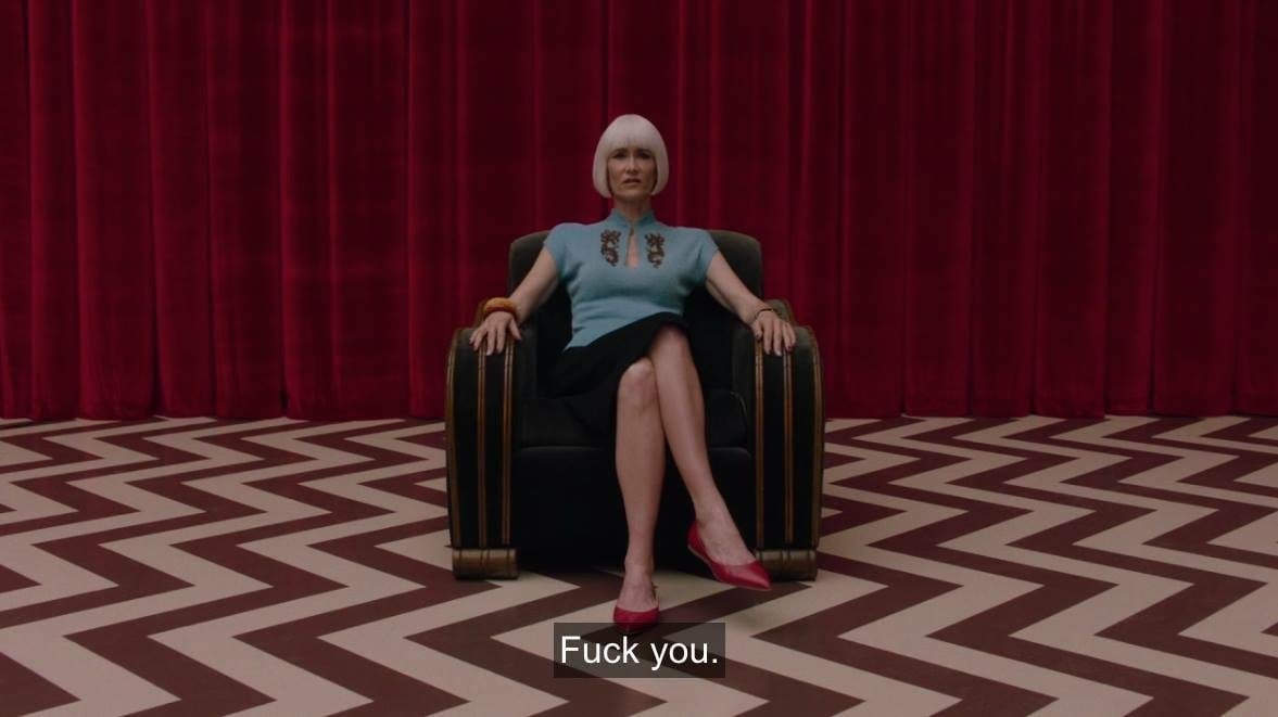 Diane sits in an armchair in the red room and says fuck you