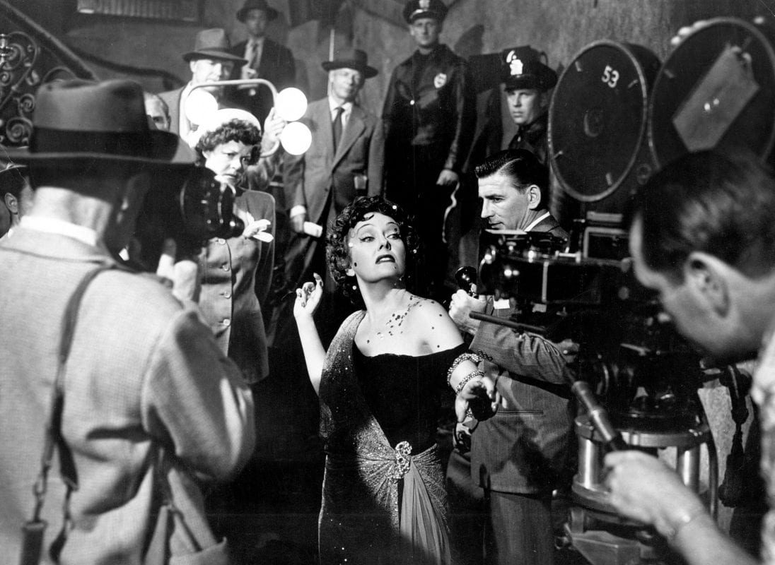 Norma Desmond ready for her closeup, surrounded by photographers and police