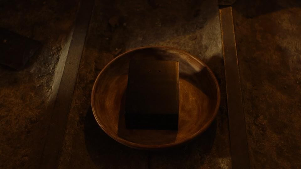 a black box in a gold sifting dish