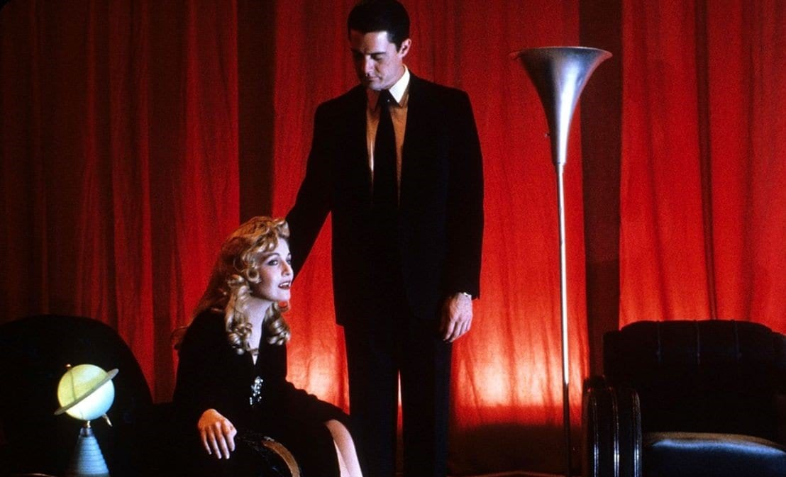 Dale Cooper rests his hand on Laura Palmer shoulder supportively in the red room