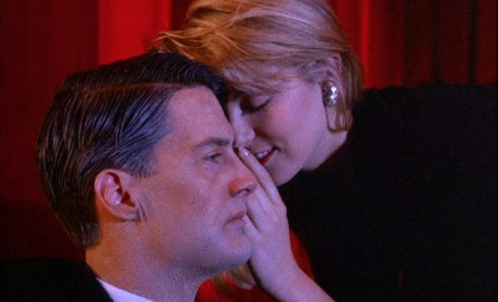 Laura Palmer whispers in the ear of an aged Dale Cooper in the red room