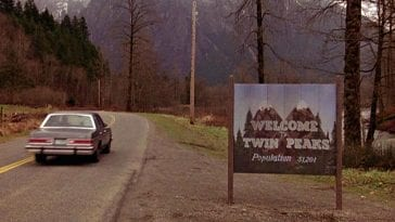 car driving by the welcome to twin peaks sign