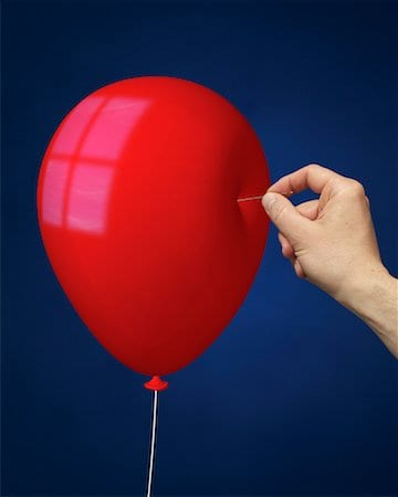 a red balloon with a hand about to stick a pin in it