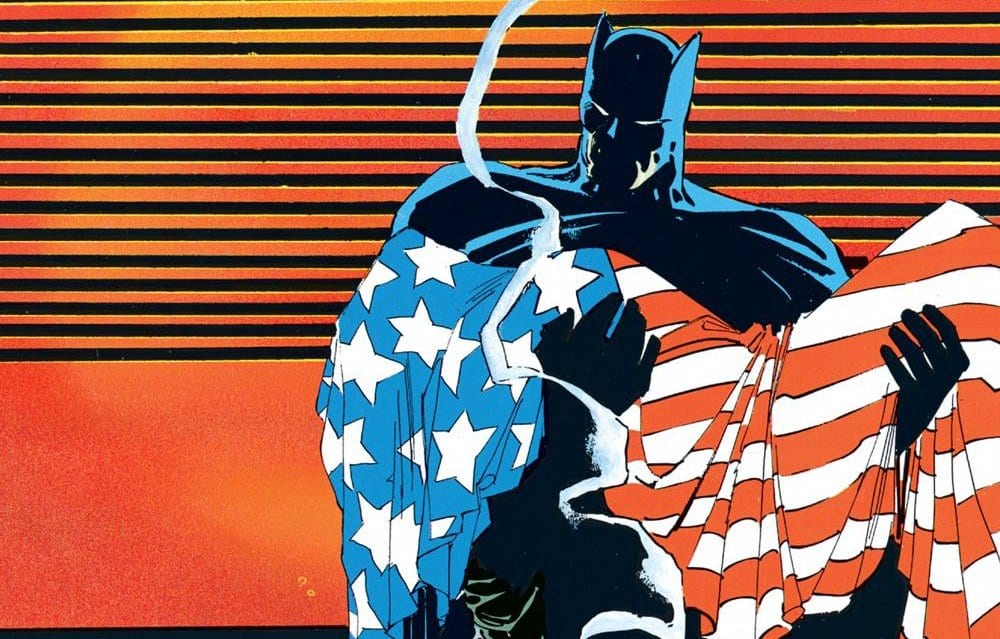 Batman carries a body draped in the American flag