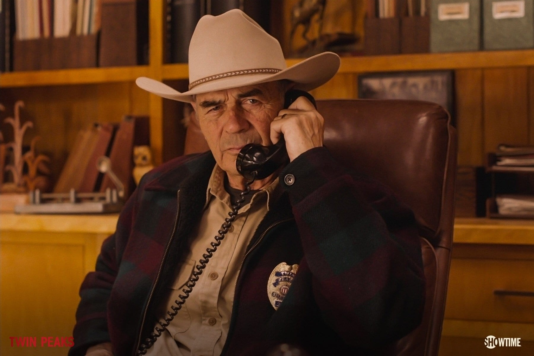 Frank Truman on the phone wearing a cowboy hat