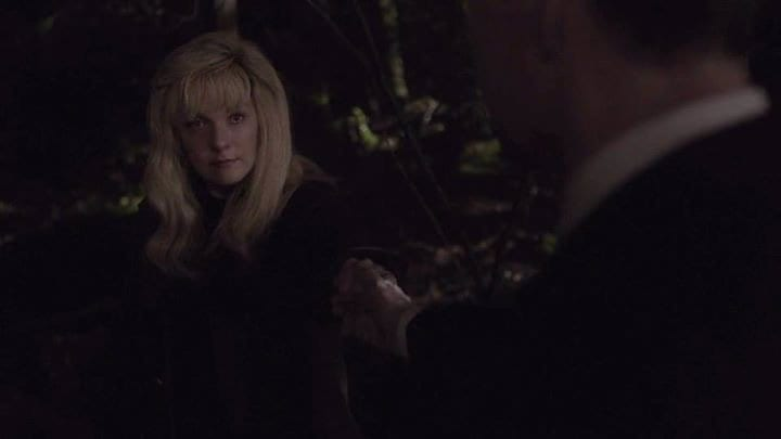 Laura Palmer takes the hand of Agent Cooper in the forest
