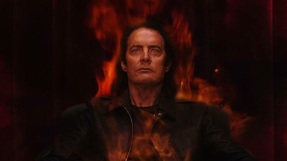 Mr C sits on a chair in the red room on fire