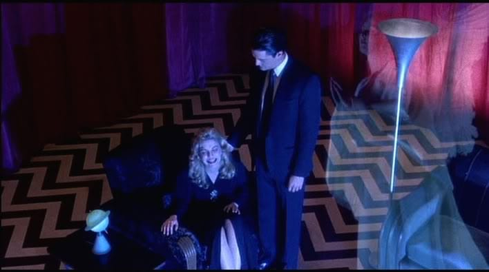 laura and cooper in the red room, laura cries with joy, cooper puts his arm around her shoulder, an angel appears to her