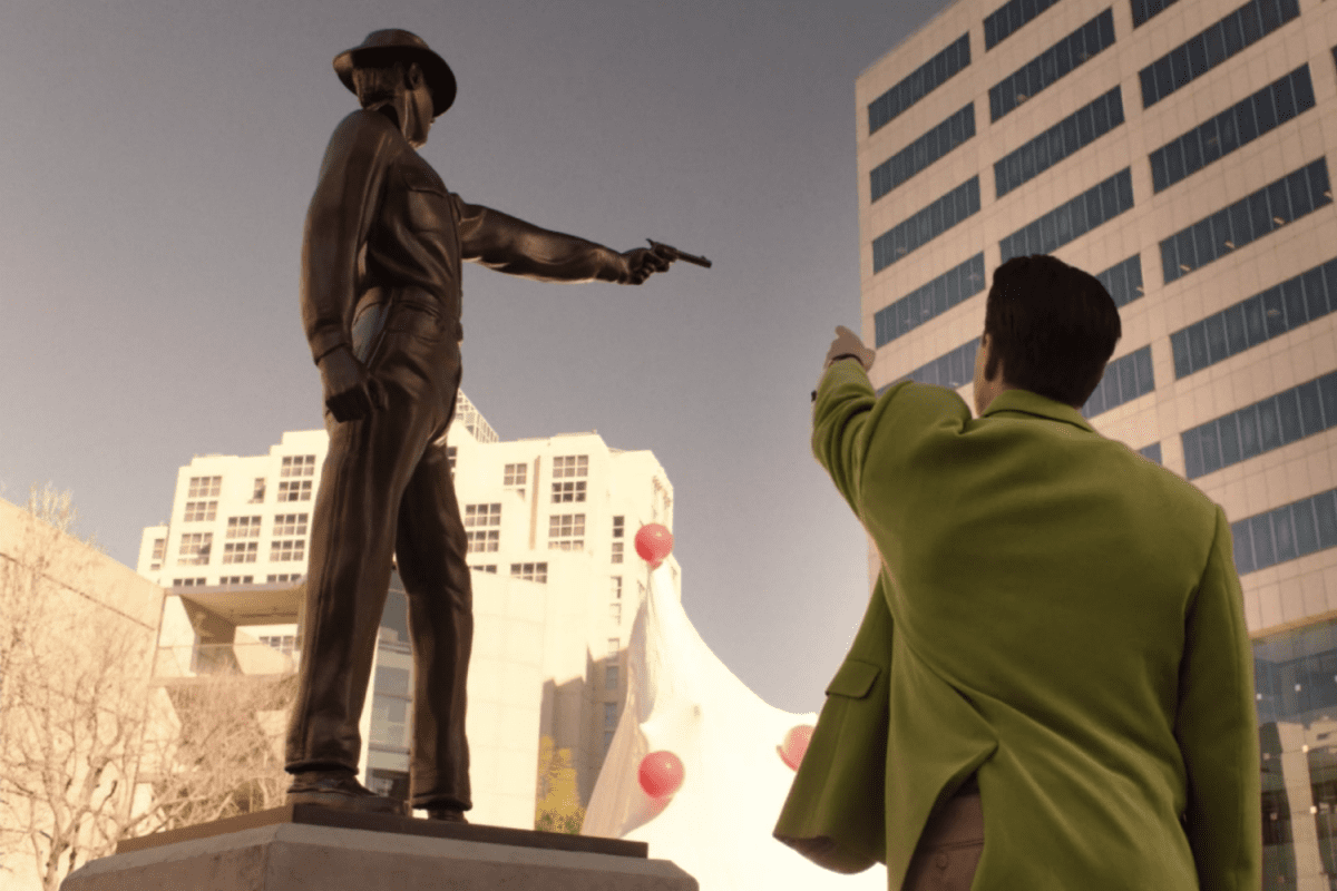 Dougie Jones mimics the bronze statue of a cowboy shooting his gun
