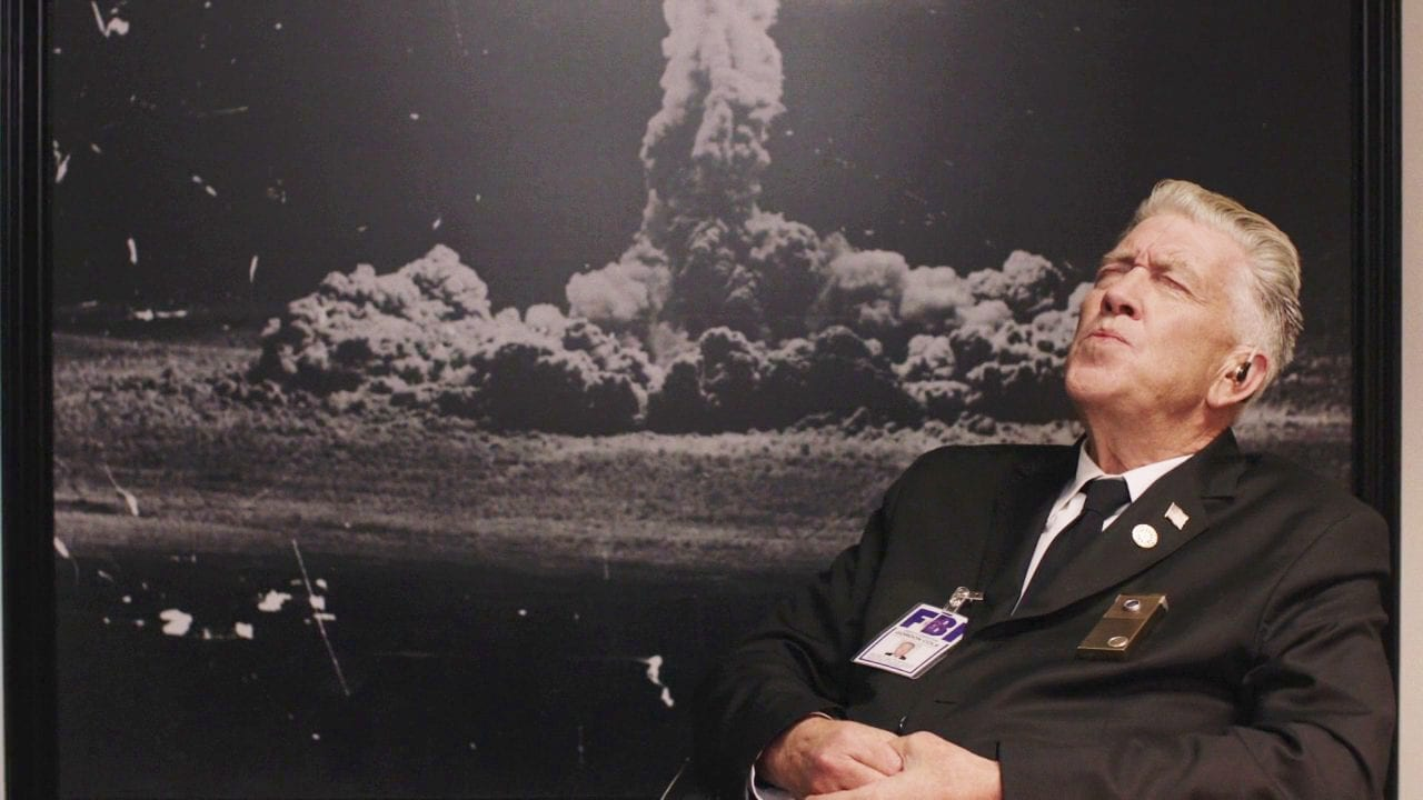 Gordon Cole whistles at his desk in front of a photo of an atom bomb explosion