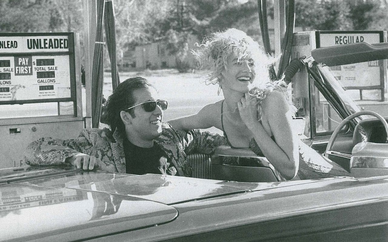 black and white pic of sailor and lula laughing in a car in wild at heart