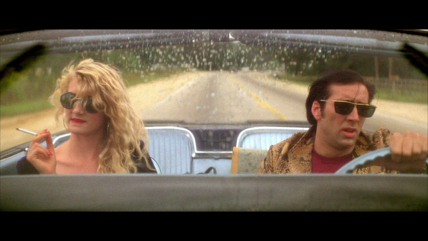 sailor and lula drive in their car in wild at heart