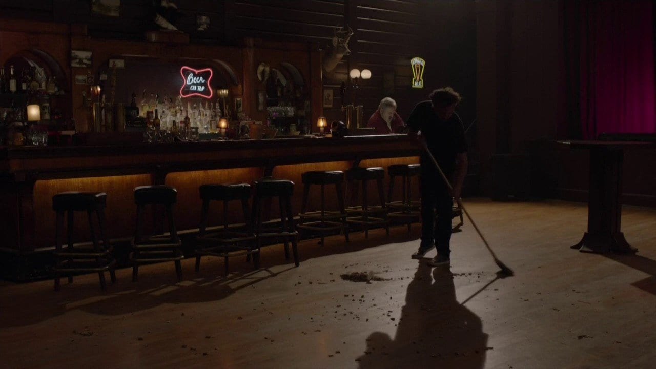 a man sweeps the roadhouse floor