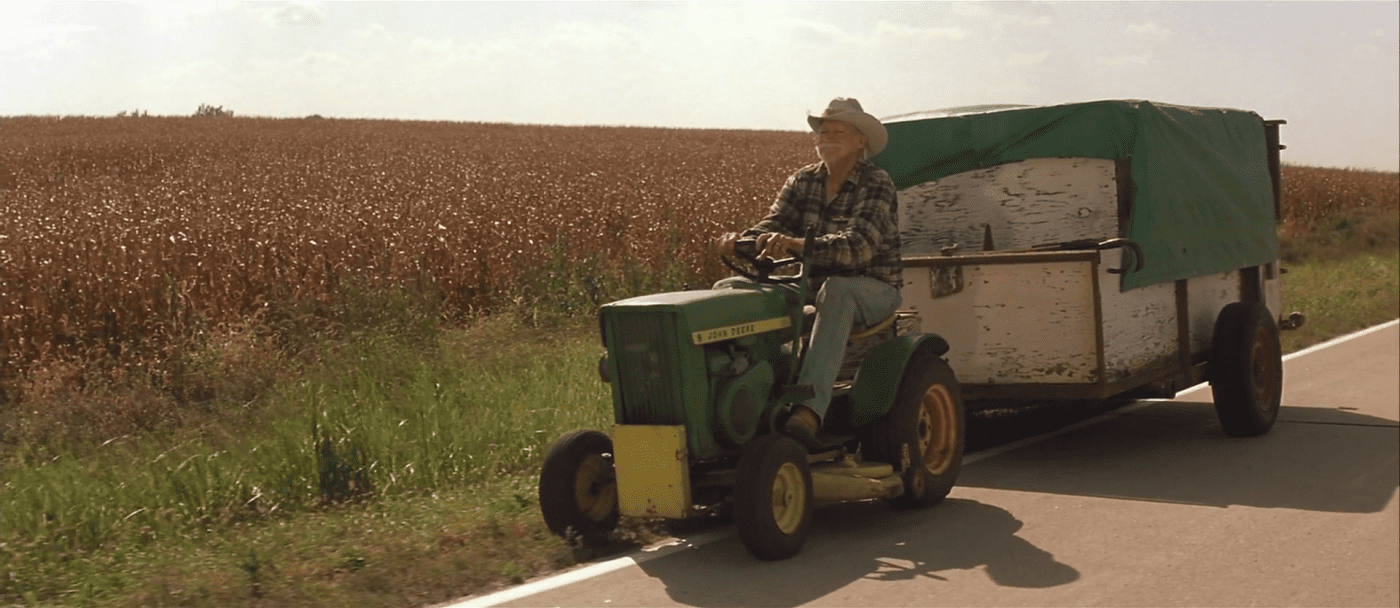 Alvin drives his tractor along the road, pulling a trailer