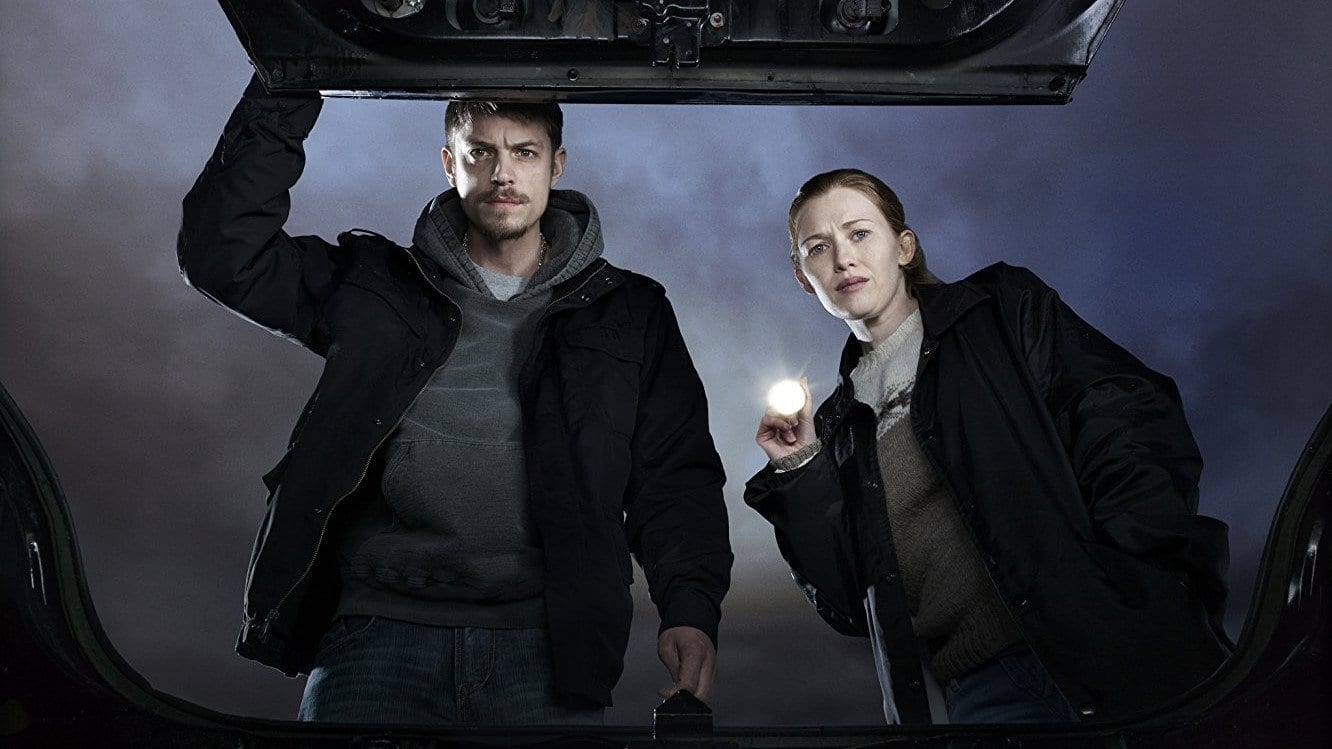 Mireille Enos and Joel Kinnaman in The Killing, looking into a car trunk with a torch