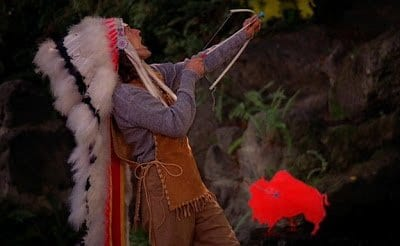 Johnny Horne dressed as a Native American, firing a toy crossbow