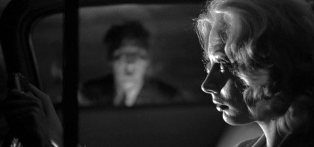 a blonde female drives her car, a blurred male face peers into her window