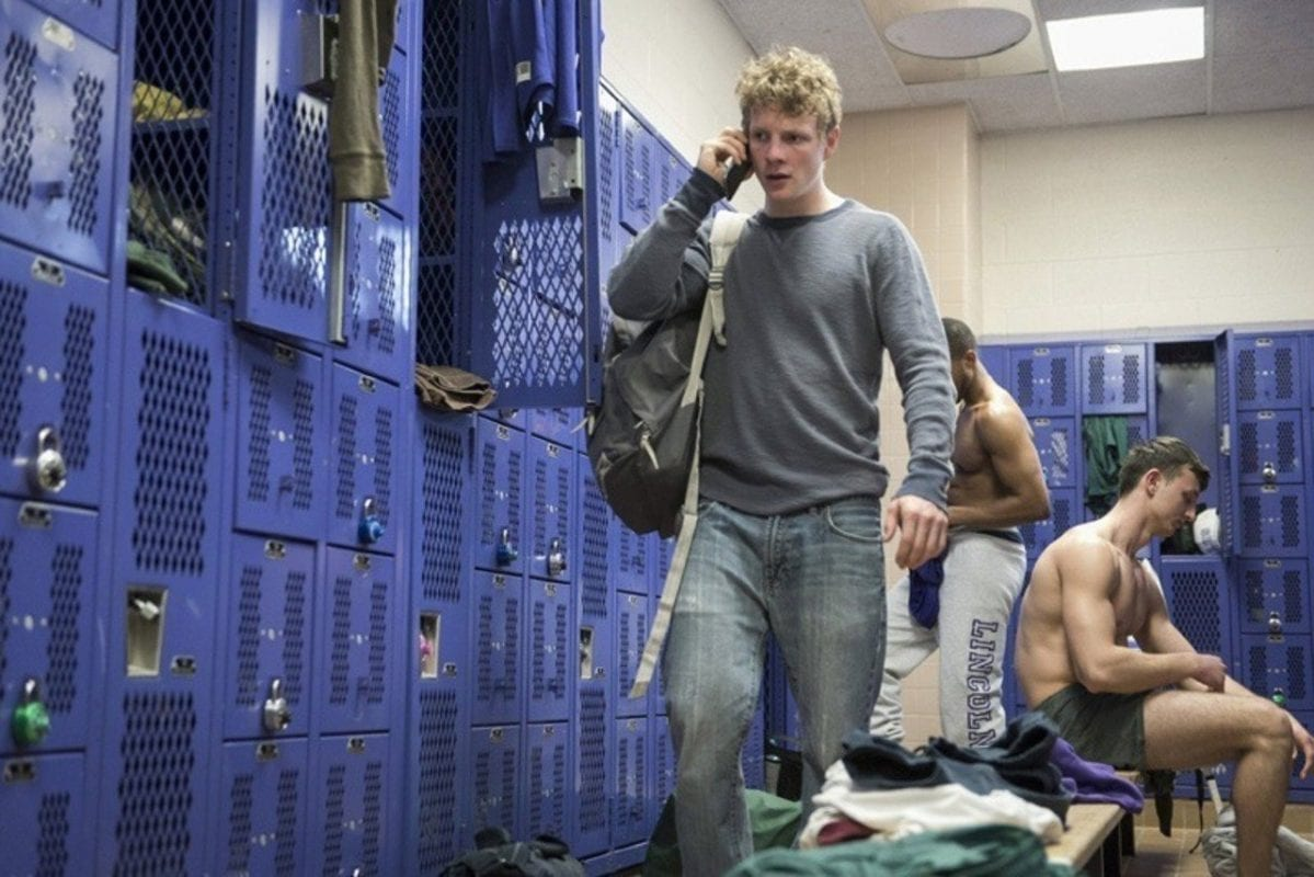 steve walks through a purple tinged locker room while on his cell phone