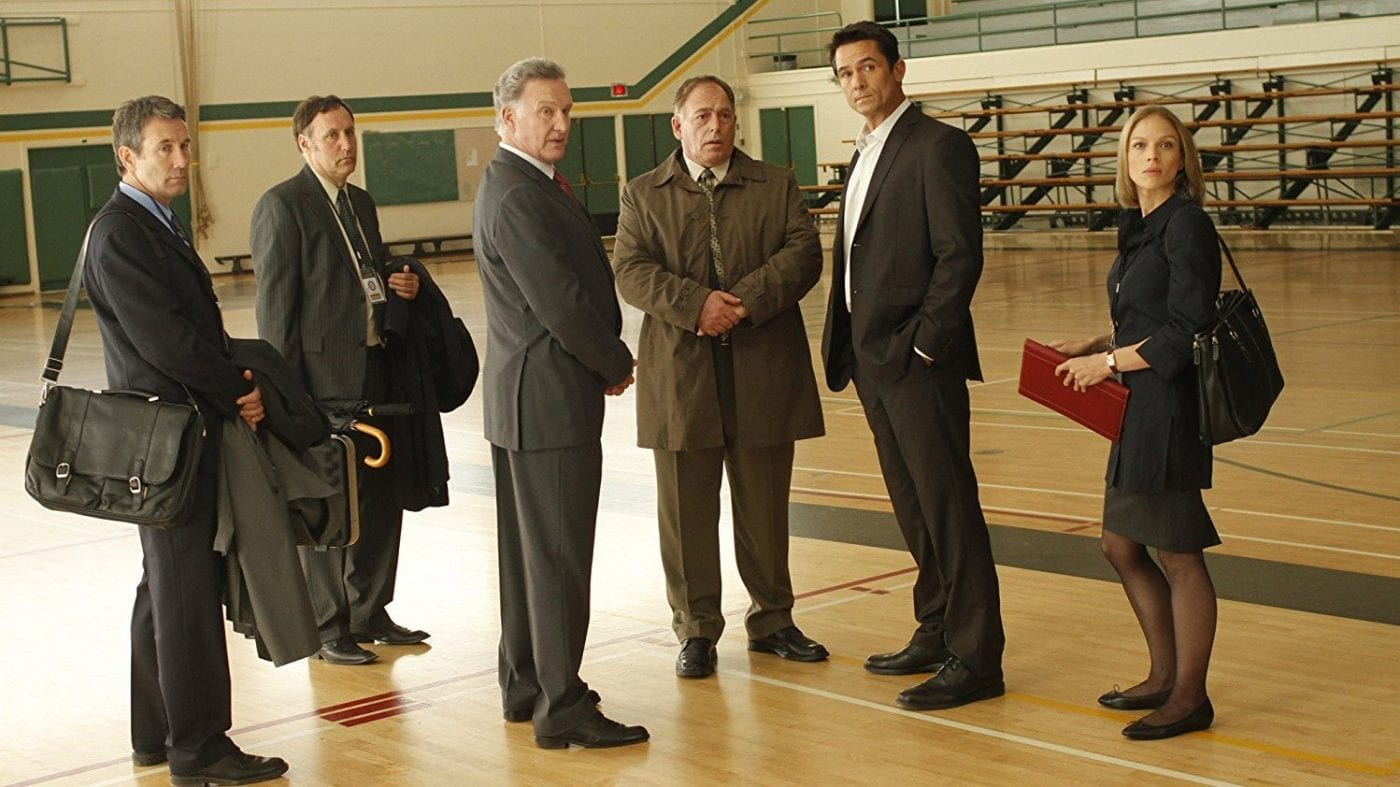 5 male politicians and 1 female intern stand in a school gymnasium