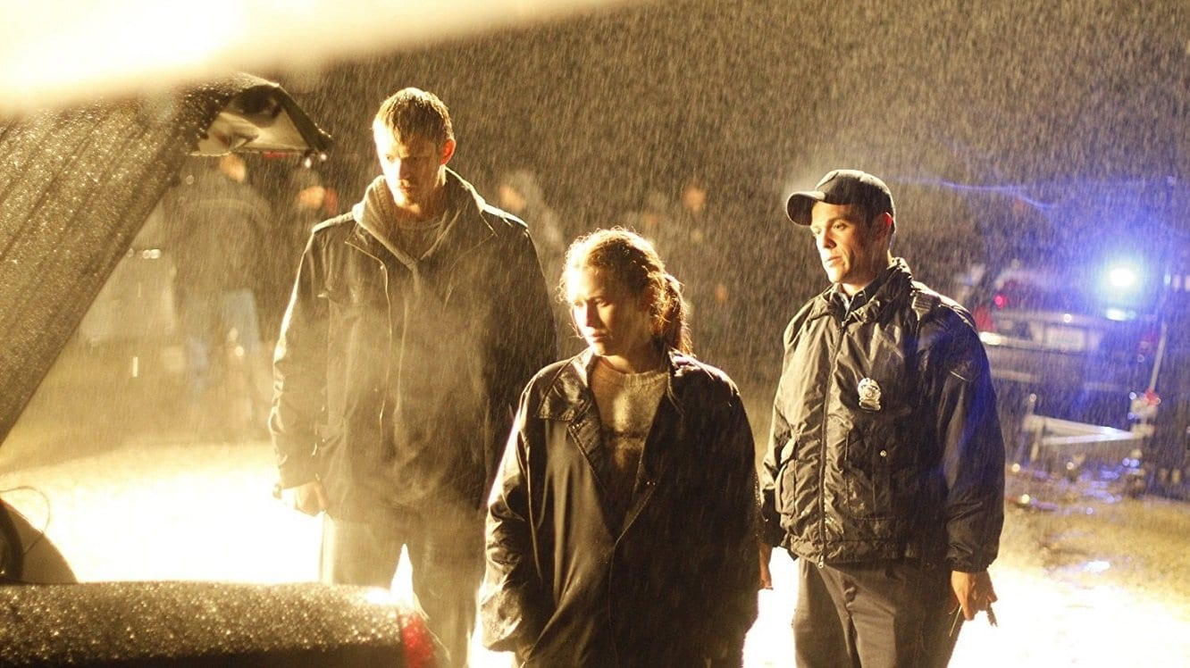 Linden and Holder look in the boot of a car alongside a police officer, at night in the rain