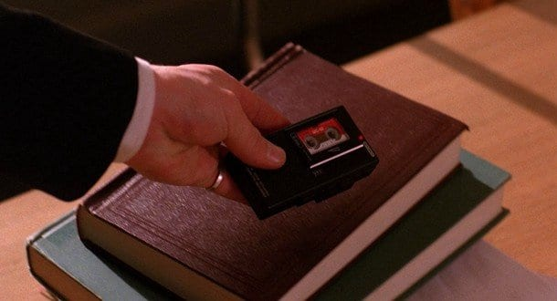 Dale Coopers hand holding a black tape recorder in front of two books