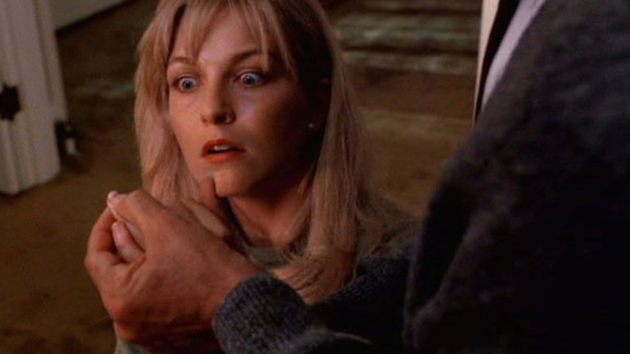 Laura Palmer looks frightened as her father checks her fingernails for dirt