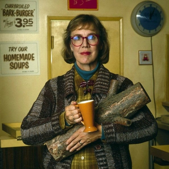 the log lady smiles with a cup of coffee and her log in her arms