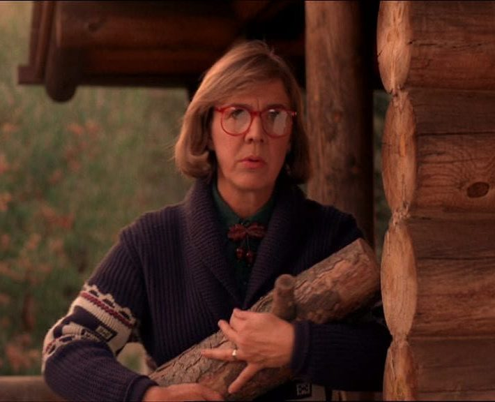 the log lady outside her cabin in the woods