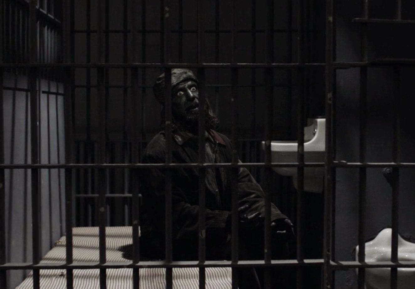 woodsman stare ahead scarily in the prison cell