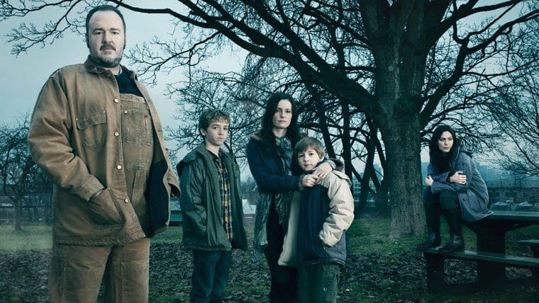 The Larsen family outside under a tree in The Killing