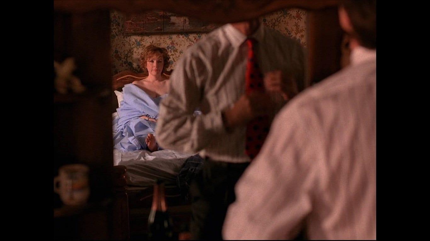 Catherine Martell lies in a motel room bed watching Ben straighten his tie in the mirror