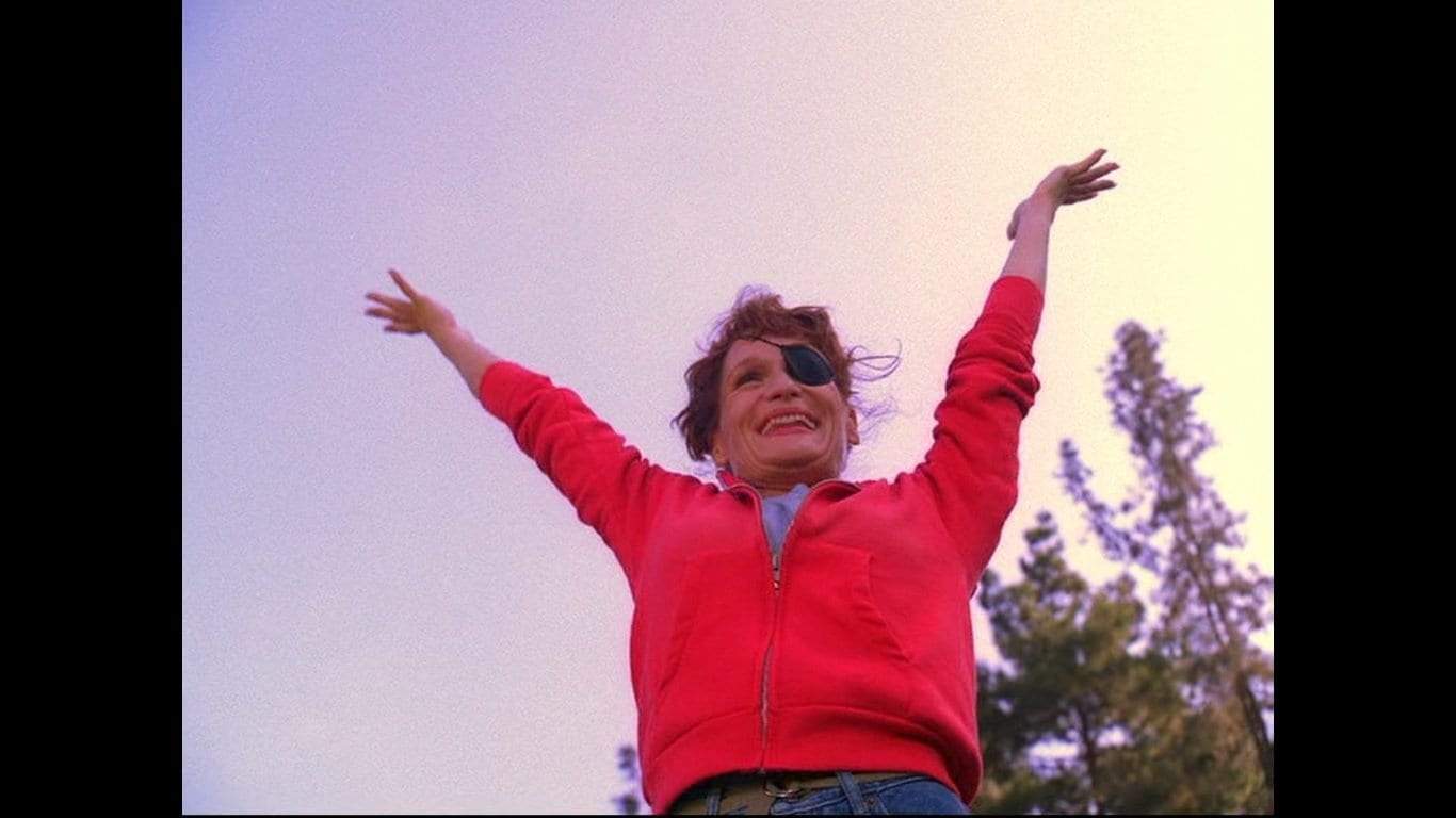 Nadine Hurley the cheerleader raises her arms in the air and grins
