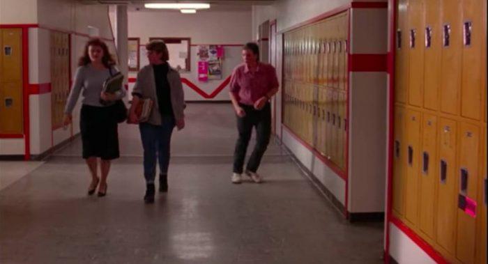Boy dances in the hallway as two girls walk down it