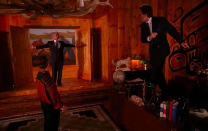 Leland stands in Bens doorway arms outstretched as Ben and Jerry dance