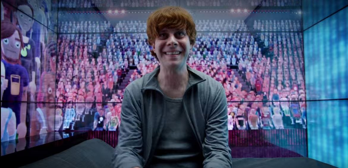 A red haired man sits in a room surrounded by virtual avatars in Black Mirror Fifteen Million Merits