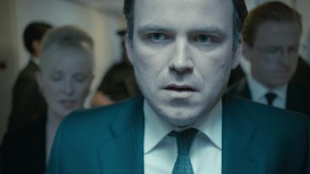 Rory Kinnear looks worried as he walks in front of his advisors