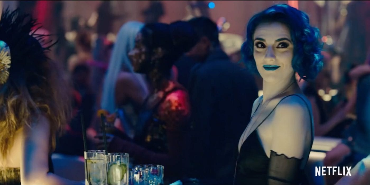 Naadirah with blue hair and lips working behind the bar in a futuristic nightclub