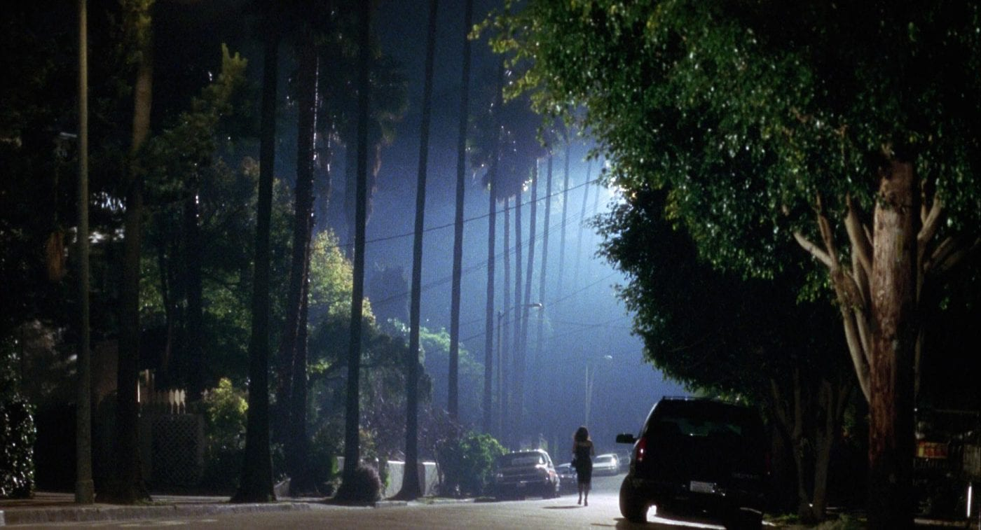 Still from Mulholland Drive. Rita wanders the streets of Los Angeles after a car crash. Extreme wide shot, dark with a harsh light, palm trees.